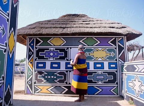Ndebele woman painting her house. South Africa.