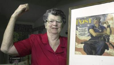 "FILE - In this May 22, 2002 file photo, Mary Doyle Keefe poses at her home in Nashua, N.H., with the May 29, 1943, cover of the Saturday Evening Post for which she had modeled as ""Rosie the Riveter"" in a Norman Rockwell painting. Keefe died Tuesday, April 21, 2015, in Simsbury, Conn., after a brief illness. She was 92. (AP Photo/Jim Cole, File) (Jim Cole/AP)"